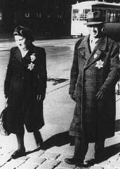 A Jewish couple wearing mandatory Jewish badges.