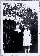 Augusta Feldhorn stands next to a nun while in hidi...