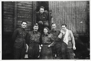 Six members of the Anders Army pose in front of a railcar...