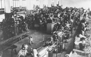 Prisoners at forced labor under SS guard in an armaments factory.