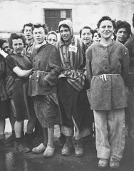 Female survivors standing outside a barracks in the...