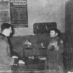 A German policeman interrogates a Jewish man accused of trying to smuggle a loaf of bread into the Warsaw ghetto. Warsaw, Poland, 1942-1943.