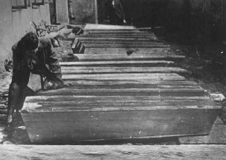 A woman mourns by the coffins of Jews who died in the Kielce pogrom. Poland, July 6, 1946.