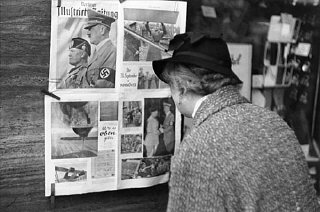 In Berlin, a German woman reads a copy of the Berliner...