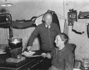 A Jewish refugee family prepares food with rations...