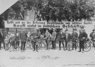 """Cartaz usado durante o boicote anti-semita: """"Ajude a libertar a Alemanha do dinheiro judeu""""."""