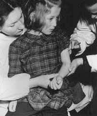 United Nations personnel vaccinate an 11-year-old concentration...