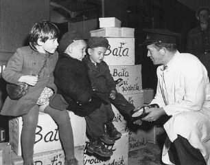 Jewish orphans fleeing Europe are fitted with shoes...