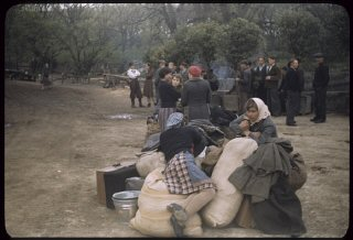 Displaced persons wait next to their suitcases and...