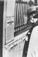 A Jewish man wearing a yellow star reads newly posted...