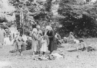 Jews who were expelled from Romania to Hungary eat in an open field.