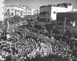 Crowds gathered in the streets of Tel Aviv celebrate the anniversary of the establishment of Israel with an independence day parade. Tel Aviv, Israel, May 1949.