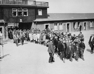 Escorted by American soldiers, child survivors of Buchenwald file out of the main gate of the camp. Buchenwald, Germany, April 27, 1945.