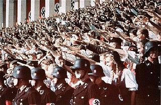 Jóvenes alemanes asistiendo al mitin de la Conferencia nacional del Partido en el Campo Zepplin de Nuremberg alzan sus manos haciendo el saludo Hitleriano. Nuremberg, Alemania, septiembre de 1938.