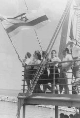 "Jewish refugee children unfurl the Jewish flag as they arrive at the Haifa port aboard Aliyah Bet (""illegal"" immigration) ship S"