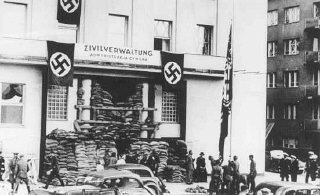 Invading German soldiers raise the Nazi flag in front...