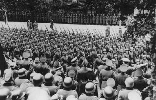 Adolf Hitler (lower right) gives Nazi salute as he...