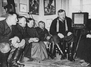 Germans listen to an antisemitic speech by Hitler.