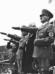 Adolf Hitler salutes the Olympic flag at the opening...