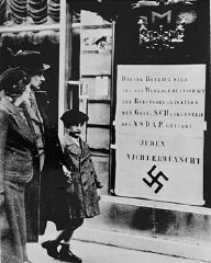 Viennese pedestrians view a large Nazi sign posted...