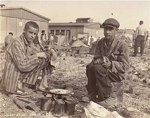 Two survivors prepare food outside the barracks. The man on the right, presumably, is Jean (Johnny) Voste, born in Belgian Congo, who was the only black prisoner in Dachau. Dachau, Germany, May 1945.