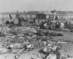 Soon after liberation, camp survivors eat near scattered...