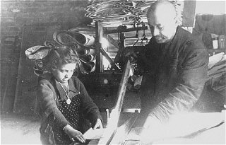 A Jewish man and child at forced labor in a factory in the Lodz ghetto.