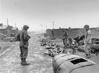 Members of the medical detachment of Combat Command A, 12th Armored Division, XXI Corps, US 7th Army, view the burned corpses of