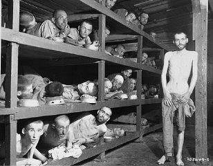 "Former prisoners of the ""little camp"" in Buchenwald stare out from the wooden bunks in which they slept three to a ""bed."" Elie Wiesel is pictured in the second row of bunks, seventh from the left, next to the vertical beam. Abraham Hipler is pictured in the second row, fourth from the left. The man on the third bunk from the bottom, third from the left, is Ignacz (Isaac) Berkovicz. [He has also been identified as Abraham Baruch.] Michael Nikolas Gruner, originally from Hungary, is pictured on the bottom left corner. Perry Shulman from Klimitov, Poland is on the top bunk, second from the left (looking up). Buchenwald, Germany, April 16, 1945."