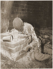 The charred corpse of a prisoner killed by the SS in...