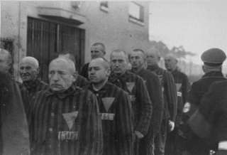Uniformed prisoners with triangular badges are assembled under Nazi guard at the Sachenhausen concentration camp.