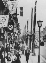A street scene showing displays of the Olympic and German (swastika) flags in Berlin, site of the summer Olympic Games. Berlin, Germany, August 1936.