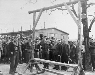 "During an official tour of the newly liberated Ohrdruf concentration camp, an Austrian Jewish survivor describes to General Dwight Eisenhower and the members of his entourage the use of the gallows in the camp. Among those pictured is Jules Grad, correspondent for the US Army newspaper ""Stars and Stripes"" (on the right). Ohrdruf, Germany, April 12, 1945."