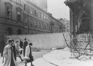 Polish civilians walk by a section of the wall that...