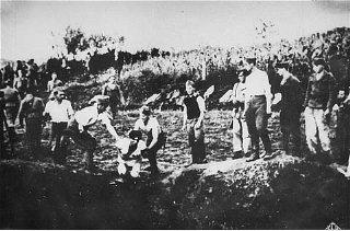Ustasa (Croatian fascist) guards force a prisoner into...
