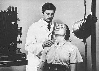 Di Institut Antropologi, Genetika Manusia, dan Eugenika Kaisar Wilhelm, seorang ahli higiene rasial tengah mengukur tubuh seorang perempuan da
