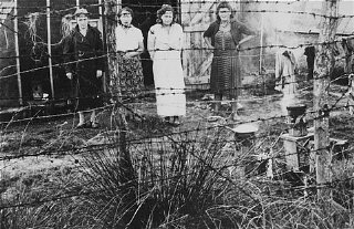 Jewish women prisoners behind a barbed-wire fence at...