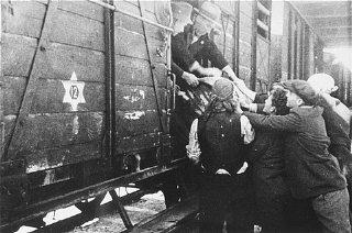 Jews load a barrel of water onto a deportation train...