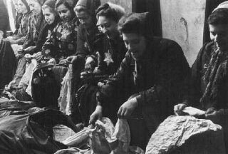 Jewish women who were seized for forced labor sort expropriated cloth.