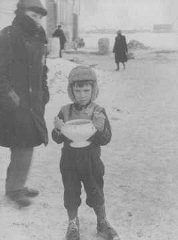 In the Kovno ghetto, a child carries a bowl of soup and holds food ration tickets.