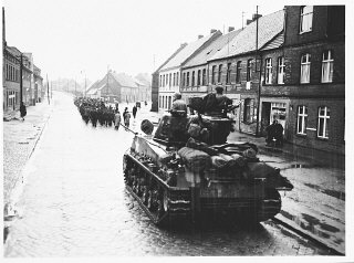 An American tank follows German civilians from Gardelegen who are marching to a barn just outside the town, where they will dig
