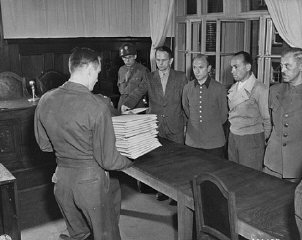 Defendant Otto Ohlendorf (second from left) receives his indictment from Colonel C.W.
