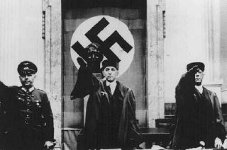 Roland Freisler (center), president of the Volk Court (People's Court), gives the Nazi salute at the trial of conspirators in th