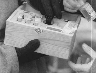 Soviet soldiers inspect a box containing poison used...