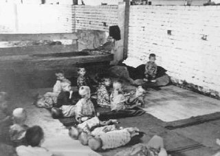 Children sit and sleep on the floor at Sisak, a Ustasa...