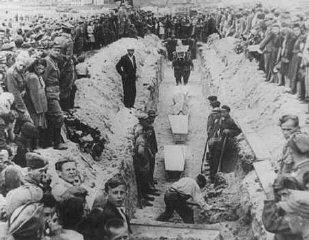 Mourners crowd around a narrow trench as coffins of...