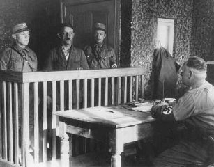 Members of the SA interrogate a newly arrived prisoner in the Oranienburg camp near Berlin.