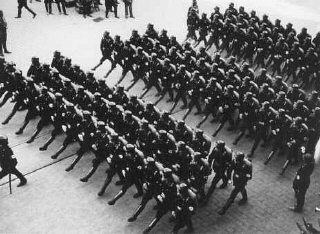 Members of the SS (Schutzstaffel; originally Hitler's bodyguard, later the elite guard of the Nazi state) parade during a rally.