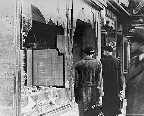 "Shattered storefront of a Jewish-owned shop destroyed during Kristallnacht (the ""Night of Broken Glass"")."
