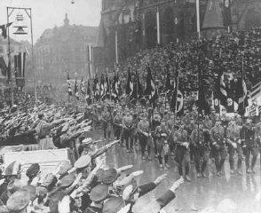 Hitler reviews a parade celebrating the reintegration...